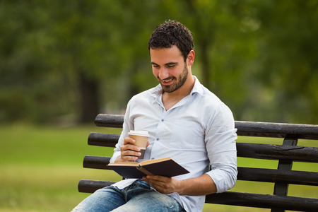 Young businessman enjoys is on a coffee break and he enjoys reading a book and sitting at the park. Imagens - 113558359