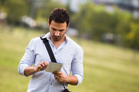 Young businessman is standing at the park and using digital tablet. Stock Photo