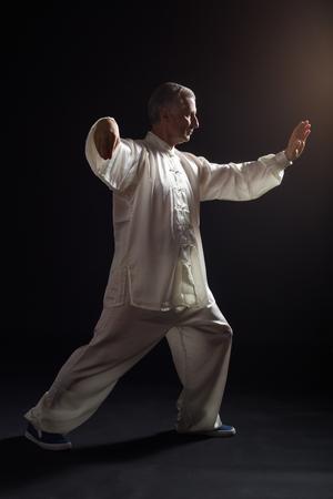Senior man enjoys exercise Tai Chi indoor. Stock Photo