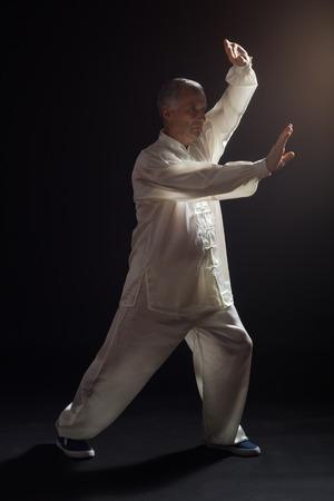 Senior man enjoys exercise Tai Chi indoor. 免版税图像