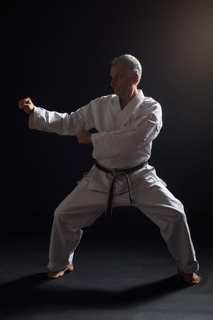 Senior man enjoys practicing karate indoor. Stock Photo