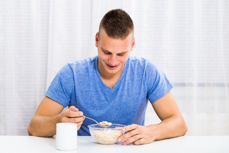 Young man enjoys having a breakfast and drinking coffee at home.