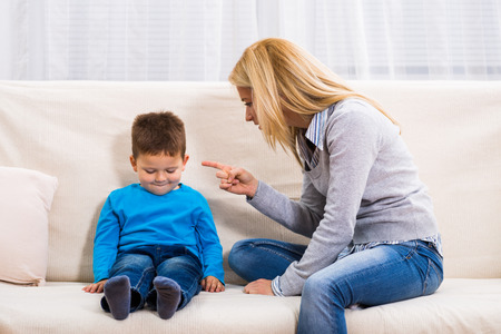 Angry mother is scolding at her son. Stock Photo