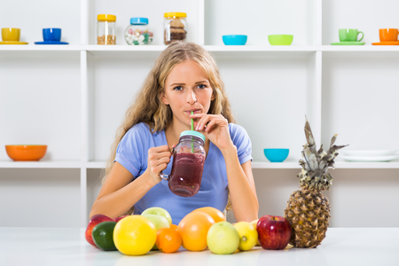 Beautiful girl enjoys drinking smoothie at her home. Imagens