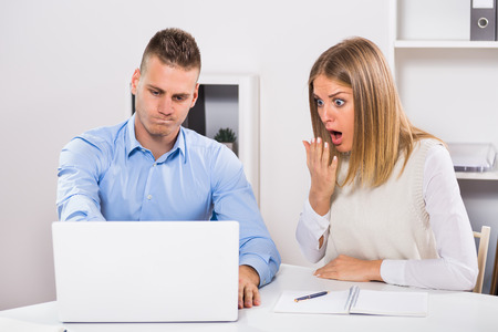 coworker: Worried businessman and businesswoman in panic are using laptop and working at their office. Stock Photo