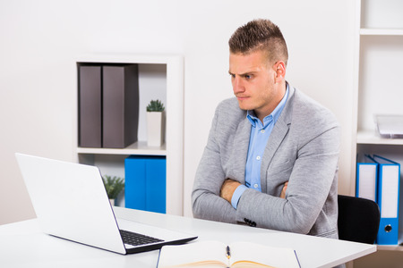personne en colere: Angry businessman is sitting at his office and looking at his laptop.