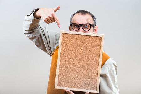 Nerdy businessman is showing empty cork board.