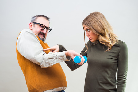 blind date: Nerdy man is flexing muscle to show a beautiful woman how strong he is and she is impressed.