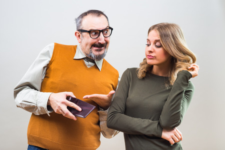 Nerdy man is trying to get attention from a beautiful woman by showing her his wallet full of money but she is still not interested. Stock Photo