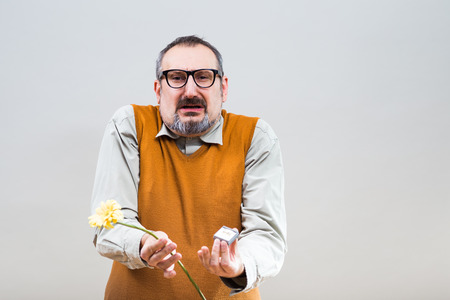 Nerdy man is very sad because he had proposal his girlfriend but she rejected him. Stock Photo