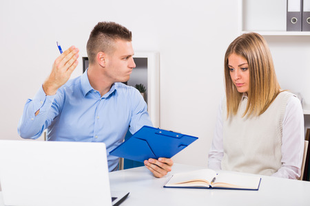 Businessman is sitting in office with his employee and he is very angry at her because of something.