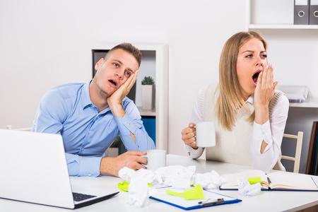 疲れのビジネスマンや実業家のオフィスでコーヒーを飲んでします。 写真素材