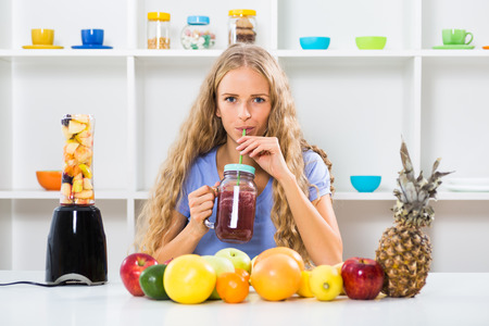 blender: Beautiful girl enjoys making and drinking smoothies at her home. Stock Photo