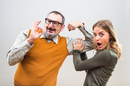 blind date: Nerdy man is showing to a beautiful woman how strong he is and she is impressed.