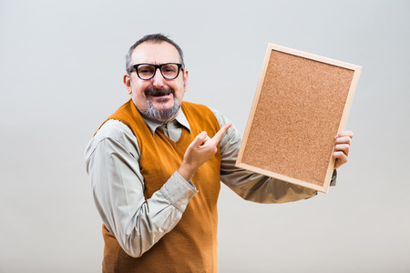 Excited nerdy businessman is showing empty cork board.