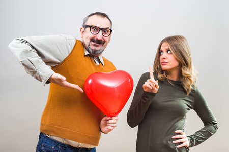 Nerdy man wants to give heart shape balloon to a beautiful woman to show her his love,but she is not interested. Stock Photo