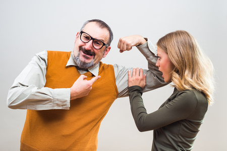 Nerdy man is showing to a beautiful woman how strong he is and she is impressed.