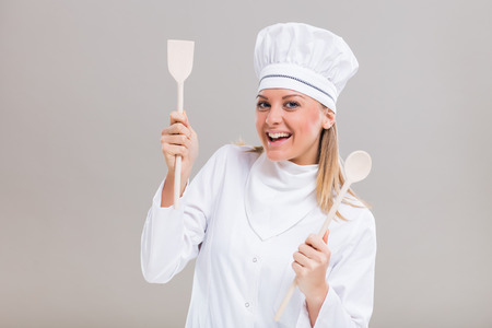 Happy female chef holding her work tool on gray background. Stock Photo