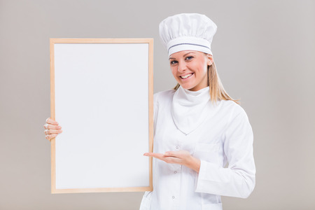 cardboard only: Portrait of beautiful female chef showing whiteboard on gray background.
