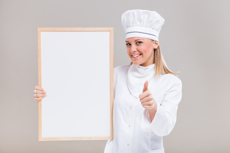 Portrait of beautiful female chef showing thumb up while holding whiteboard on gray background.