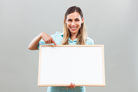 Beautiful nurse is holding whiteboard and pointing.