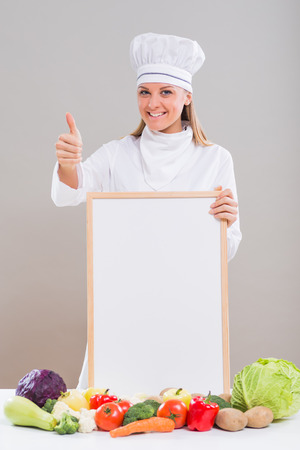 Female chef with whiteboard and vegetables showing thumb up