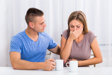 Husband is consoling his wife because she feel nausea. Stock Photo
