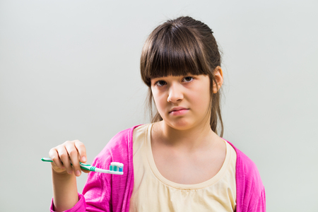 Sad little girl with toothbrush on gray background.