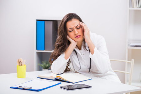 Sad Female Doctor Sitting At The Medical Office. Stock Photo ...