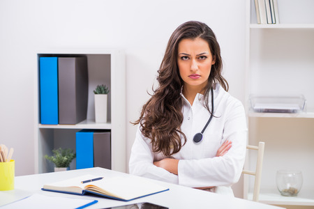 Angry female doctor sitting at the medical office. Stock Photo