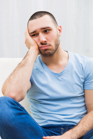 Depressed young man is sitting at the sofa and thinking about something. Stock Photo