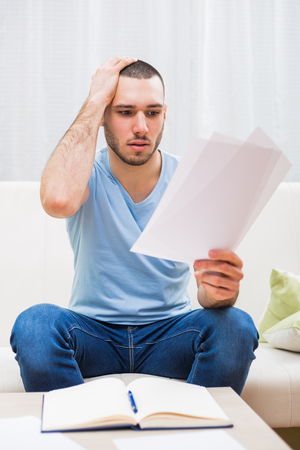 disbelief: Young man looking at his document in panic while working at his home.
