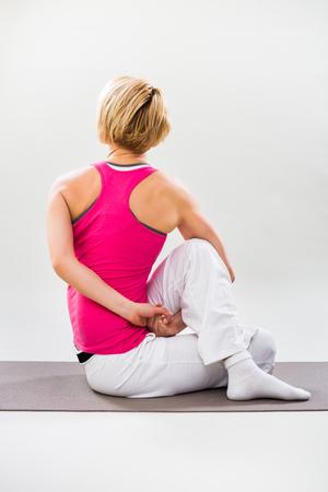 buena postura: Woman exercising yoga indoor-Spine-Twisting Pose Matsyendrasana
