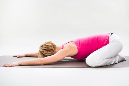 Woman exercising yoga indoor-Hare pose Shashankasana Stock Photo