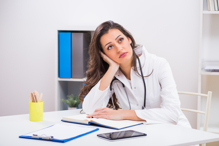 Sad female doctor thinking about something while working at her office.