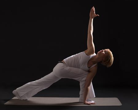 buena postura: Woman exercising yoga indoor on black background,Bikram triangle Trikonasana Foto de archivo