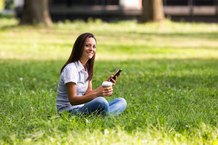 Beautiful businesswoman is drinking coffee and using phone at the park. Stock Photo