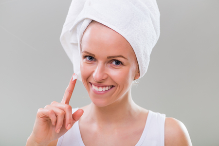 Beautiful young woman showing moisturizer on gray background.