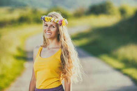 Portrait of beautiful woman with wreath on her blonde hair standing at the country road.Image is intentionally toned.