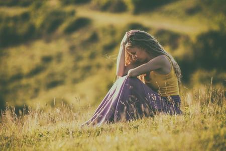 悲しい女性の自然の中で座っていると考えます。画像は意図的にトーンダウンです。