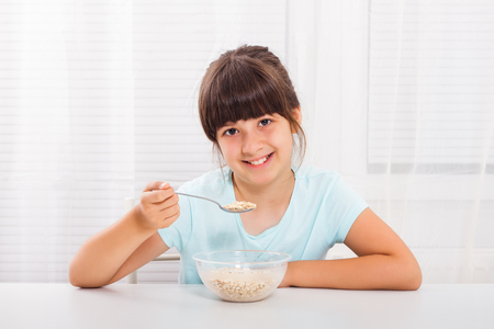 processed grains: Cute little girl is sitting at the table and eating cereals for breakfast. Stock Photo