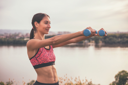 bodycare: Beautiful young woman exercising with weights outdoor.Image is intentionally toned. Stock Photo
