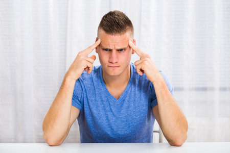 Young man is having strong headache. Stock Photo