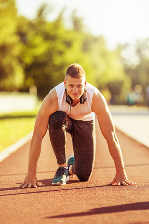 Young man at start position for running at the track.Image is intentionally toned. Stock Photo