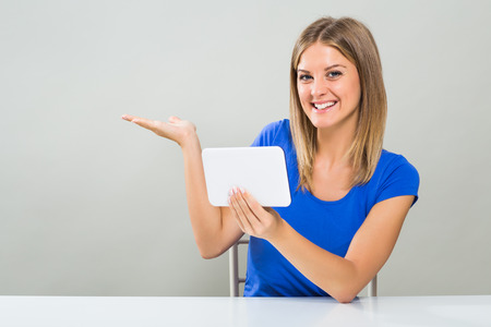 Beautiful young woman is gesturing while using digital tablet. Stock Photo