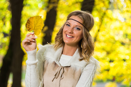 Beautiful boho girl holding autumn leaf and enjoys in the park. Imagens