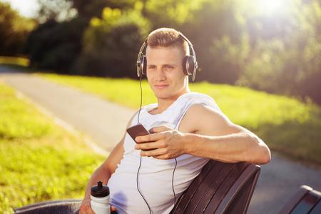 헤드폰 및 벤치에 운동 후 쉬고 물 가진 젊은 남자. 이미지는 의도적으로 톤의. 스톡 콘텐츠