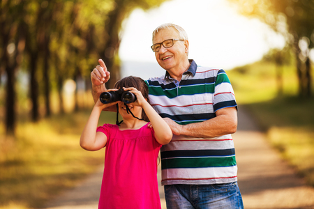 Happy grandfather and granddaughter spending time together in nature.Image is intentionally toned