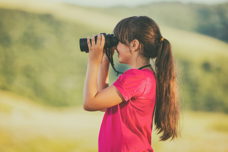 Beautiful little girl enjoys in nature with binoculars.Image is intentionally toned.