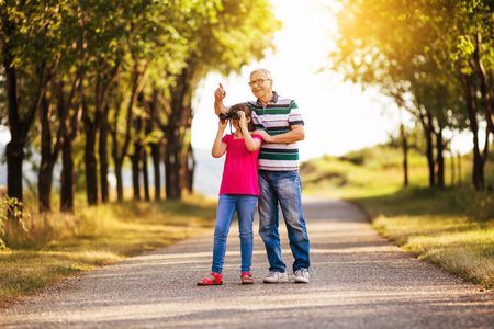 avocation: Happy grandfather and granddaughter spending time together in nature.Image is intentionally toned. Stock Photo